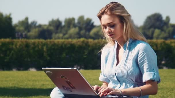 Young blonde girl typing on laptop and looking at camera