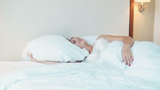 Žena spí v posteli v hotelovém pokoji