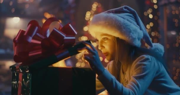 Glückliches Mädchen öffnet magisches Geschenk an Heiligabend