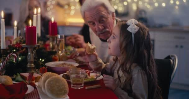 Little girl and grandpa talking on Christmas dinner