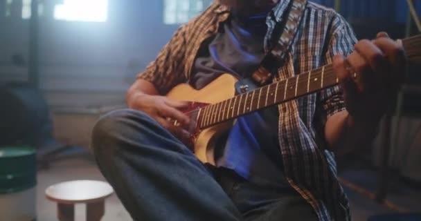 Erntehelfer spielt Gitarre in Garage