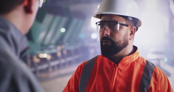 Bärtiger Inspektor spricht mit Arbeiter in Fabrik