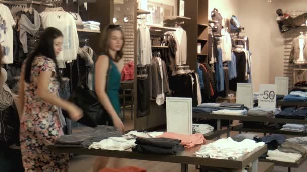Dvě mladé dívky si vybrat oblečení v obchodě