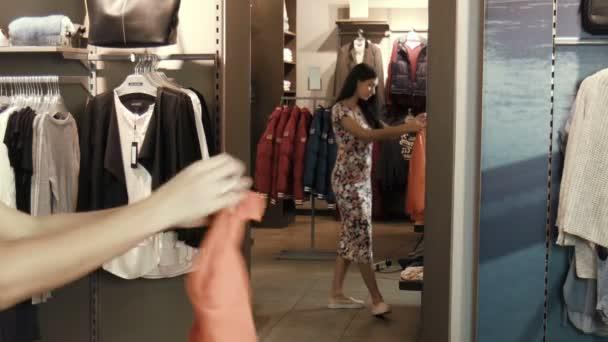 das Mädchen probiert eine Bluse in der Nähe des Spiegels an