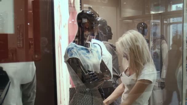 The girl the seller dresses a mannequin