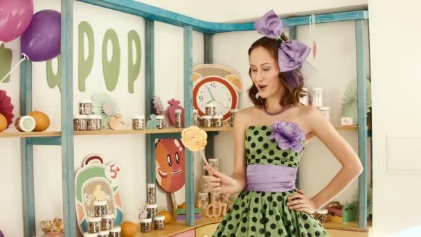 Das Mädchen in einem hellen Kleid beißt großen Bonbon am Stiel