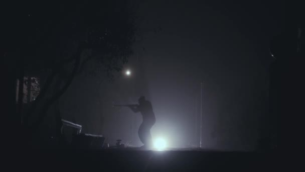 silhouette of the person with the rifle in the dark.