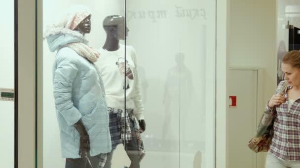 Dívka se dívá na show okno obchod s oblečením v obchoďáku