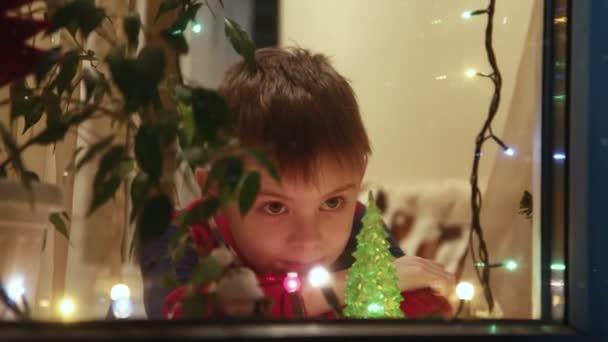 Junge schaut aus dem Fenster auf Schnee