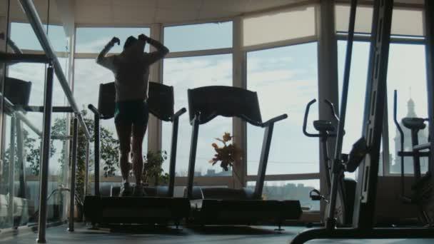 Atraktivní žena běží na běžeckém pásu v tělocvičně sportu