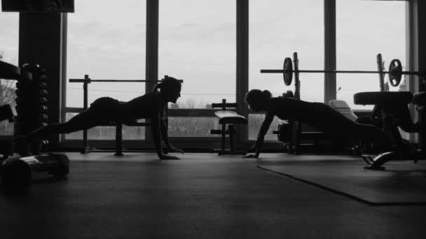 silueta, dvě holky dělat kliky v tělocvičně