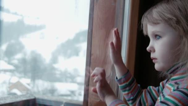 Roztomilá holčička za oknem v zimě