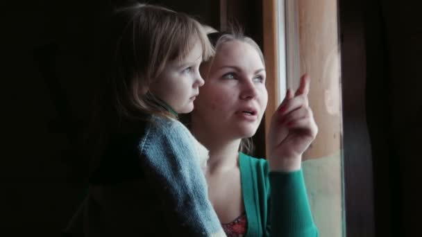 Mother shows to the daughter in a window