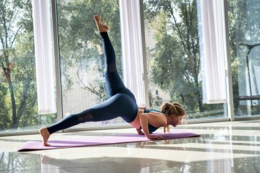 Woman wear sport clothes practicing yoga for health, help ease back pain near windows in home