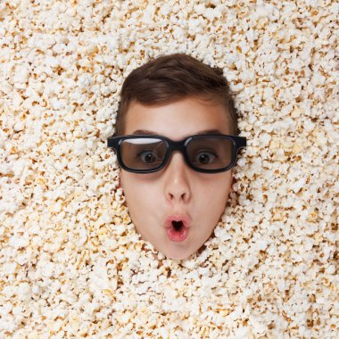 Surprise young boy in stereo glasses looking out of popcorn