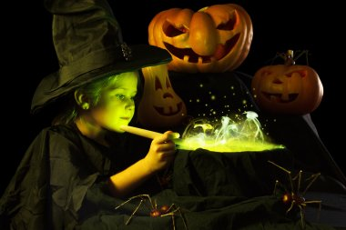 Little witch cooks a magic potion on Halloween.