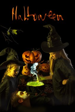 Two little witch cooks a magic potion on Halloween.