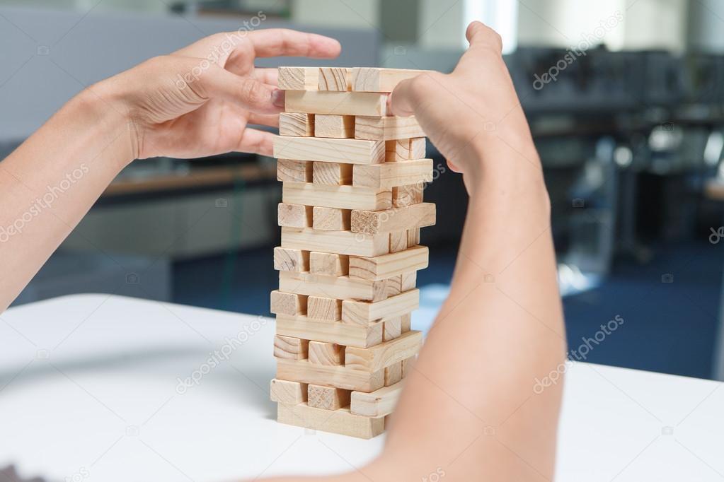 Homme qui joue avec le jeu de bois jenga dans le bureau
