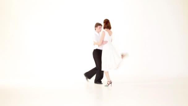 young couple showing dance moves on white background