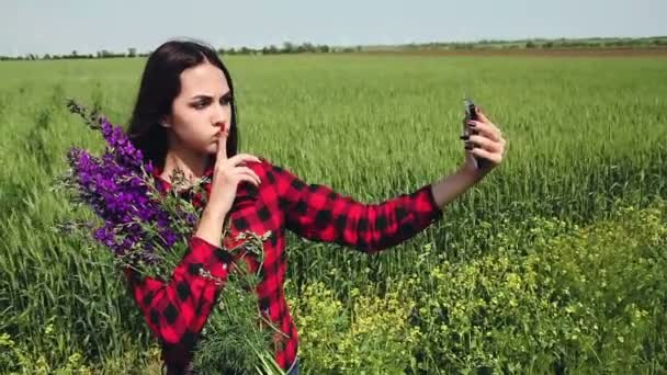 Young woman brunette with a bouquet of wildflowers makes selfie.