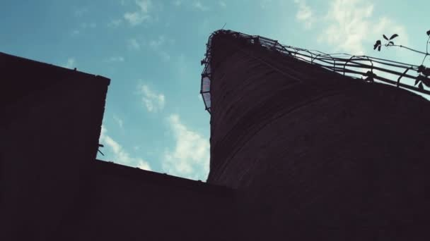 zaniklé průmyslové cihlový komín proti jasně modré obloze