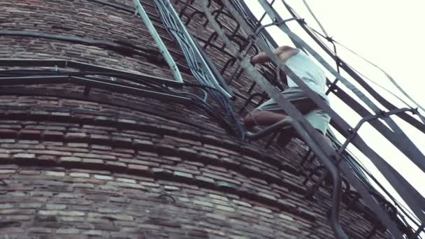 Extrémní sporty. Mladí muži sestupují Kovové schody cihlové tovární komín