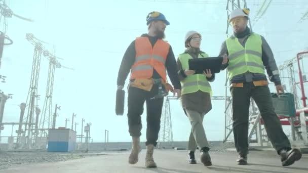 Ein Team von Ingenieuren geht durch ein Hochspannungsumspannwerk