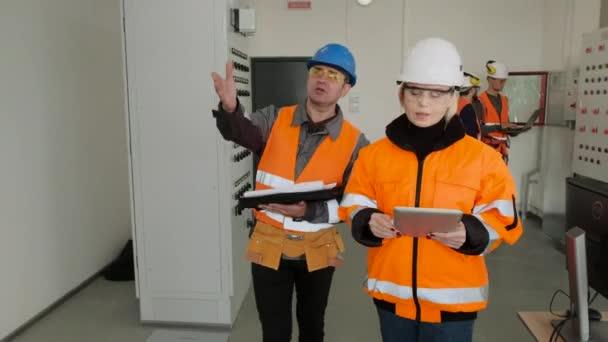 Techniker und Ingenieur mit Tablet und Papieren im Umspannwerk
