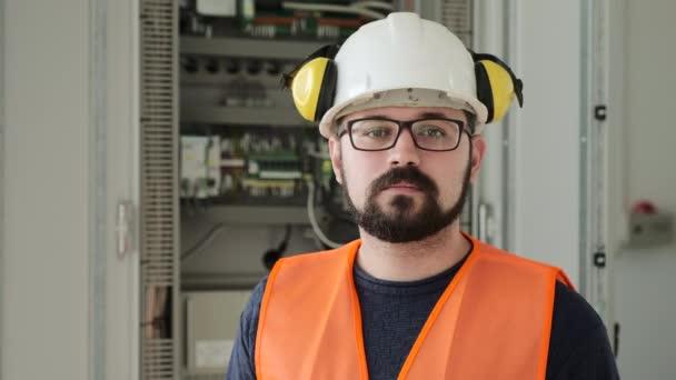 Vousatý pracovník v helmě se sluchátky poblíž ústředny