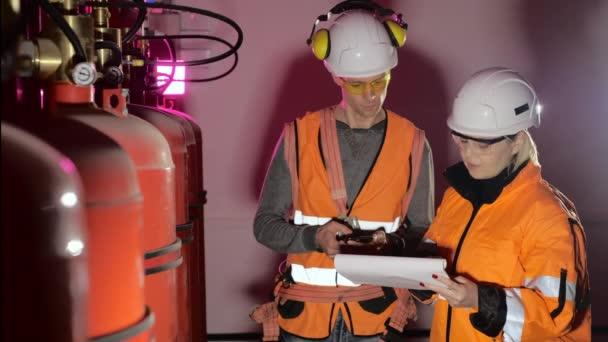 Frau mit Papieren und Arbeiter mit Taschenrechner überprüfen Gastanks