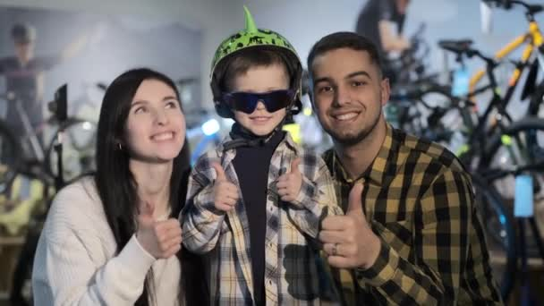 Family of mother father and son shows thumbs-up in shop