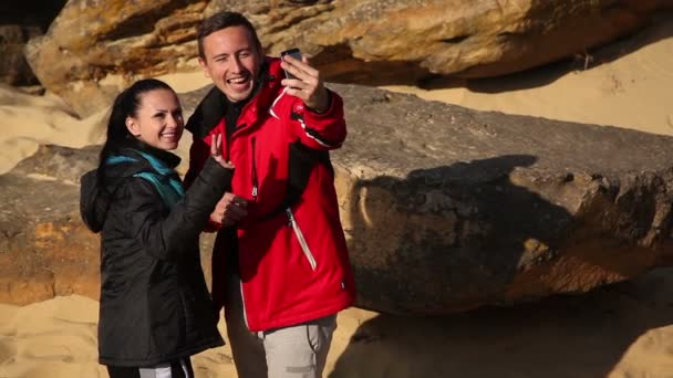 Selfie - Happy couple taking self portrait photo hiking. Two friends or lovers on hike smiling at camera outdoors.