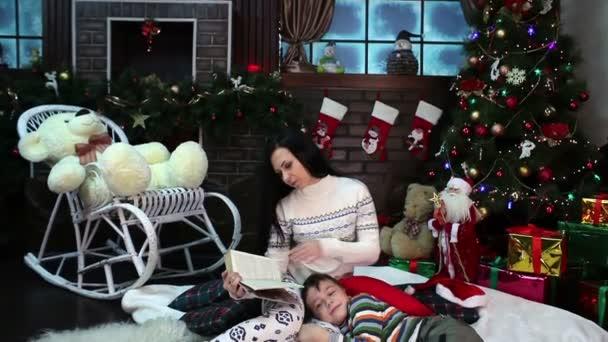 Nový rok. Vánoce. Máma a syn poblíž vánoční strom a krb. Útulný dům, vánoční nálada
