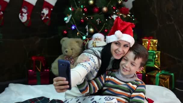 Neujahr. Weihnachten. Mutter und Sohn in der Nähe von Weihnachtsbaum und Kamin. Gemütliches Haus, Weihnachtsstimmung.