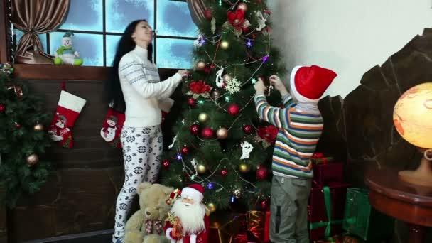 New Year. Christmas. Mom and son near Christmas tree and fireplace. Cosy house, Christmas mood.