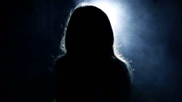 Terror. Chica en un cuarto oscuro delante de la brillante luz de la ...