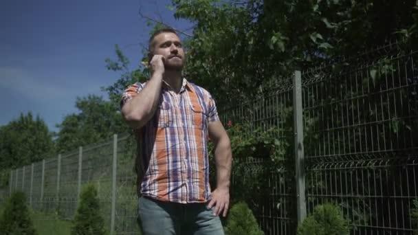 Člověk mluvící smartphone v zahradě.