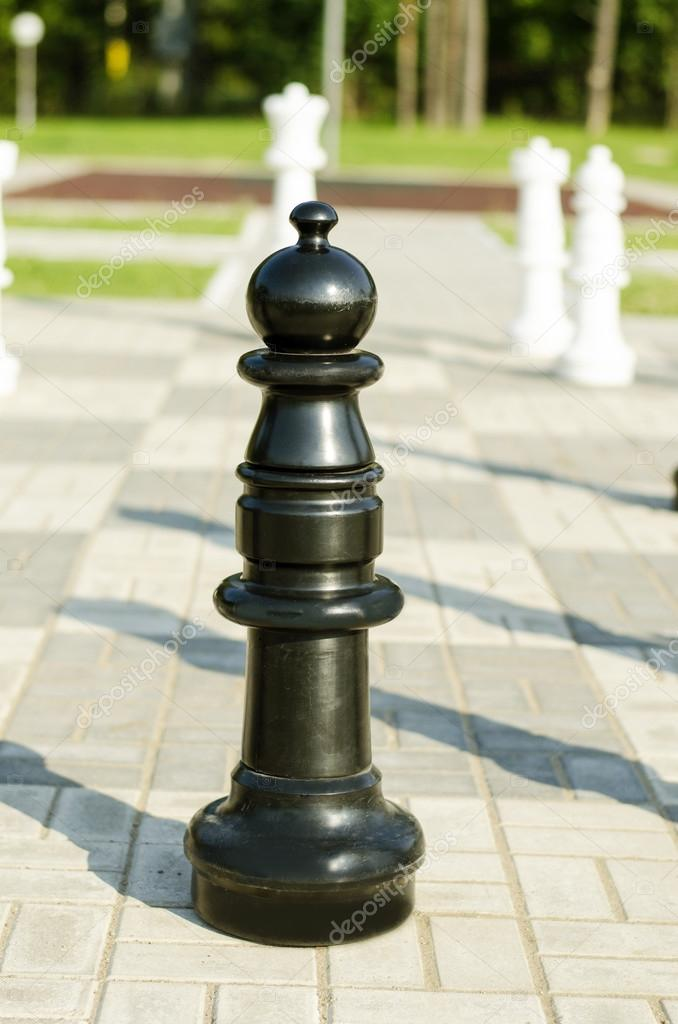 Chessman  black pawn is in the street on the stone chessboard