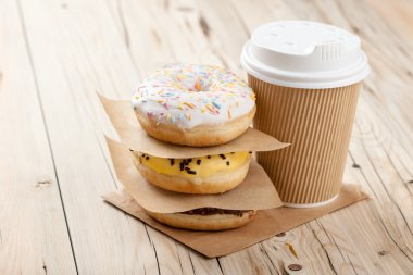 Colorful donuts and paper cup on wooden table