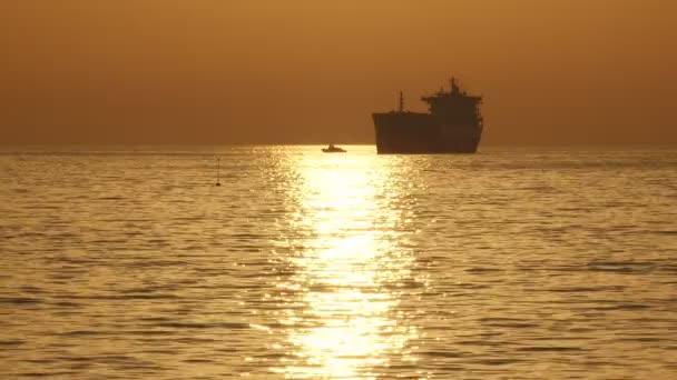 silueta nákladní lodi při západu slunce