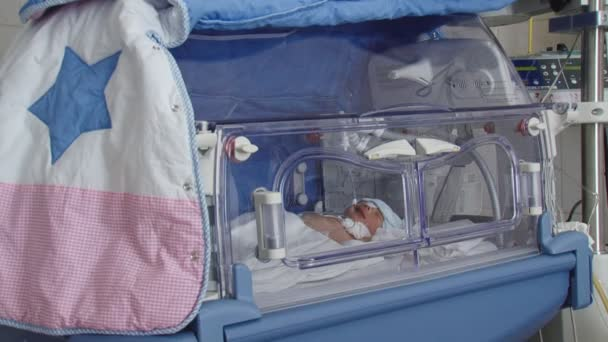newborn baby in a special box for premature babies