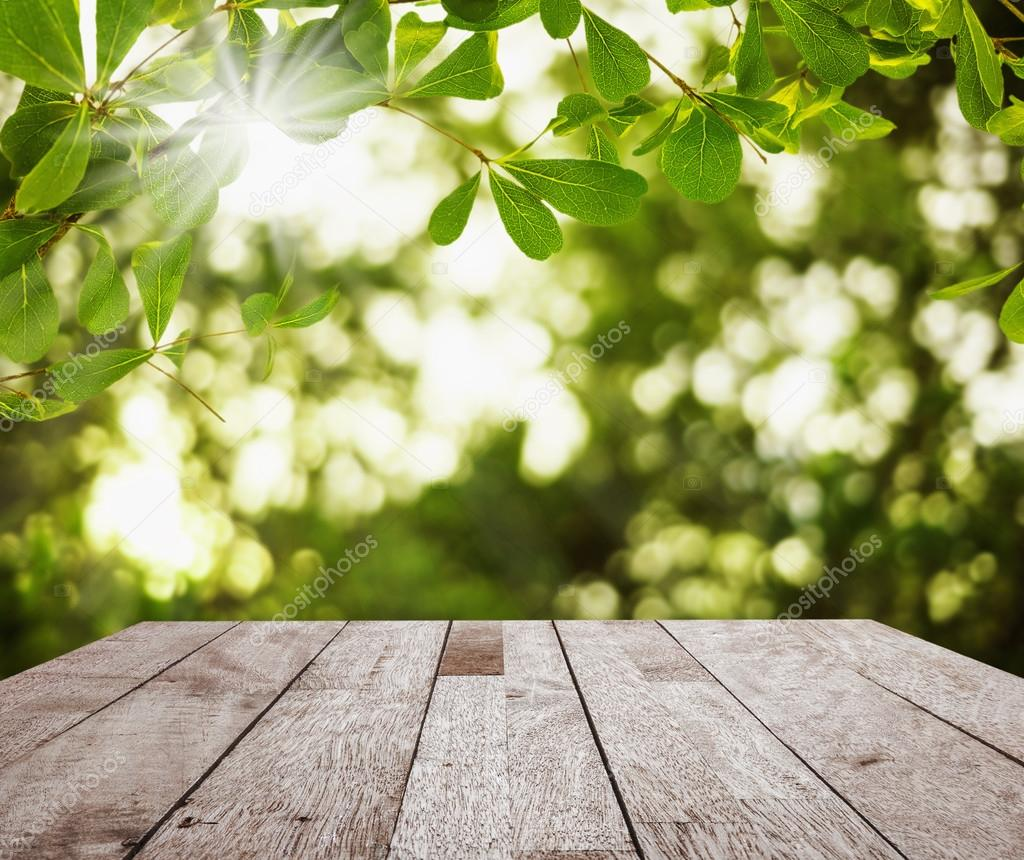 Wood table top on green leaf with light bokeh