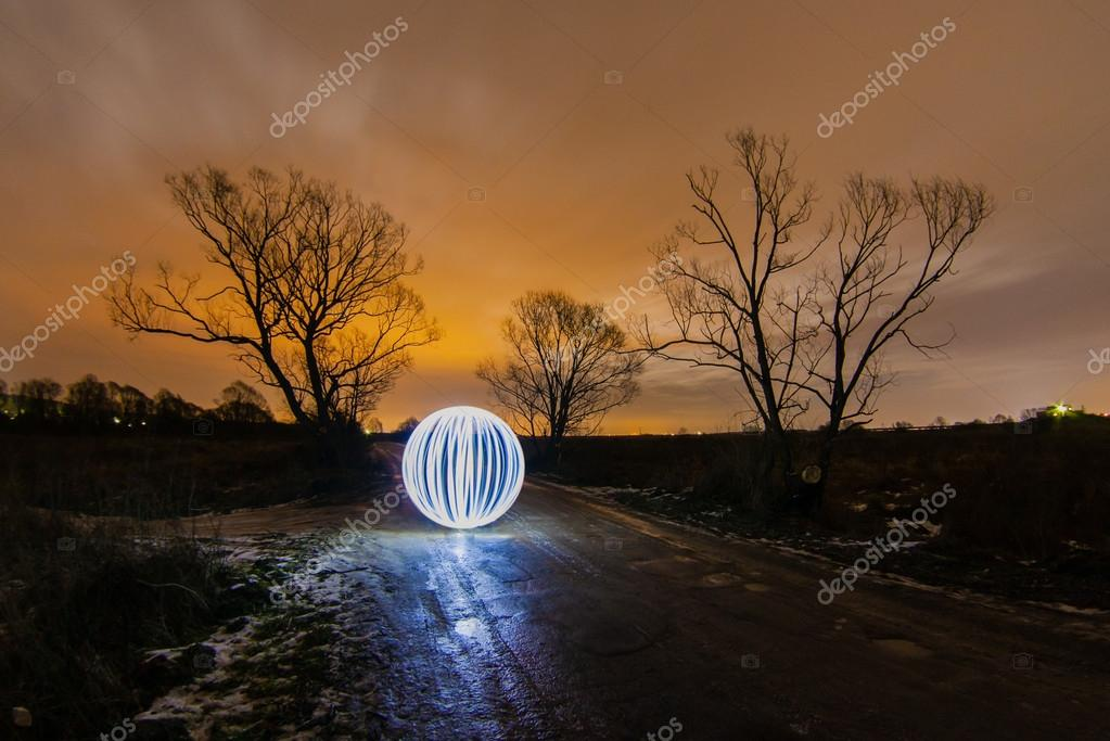 Glowing ball on spring road between two trees in a full moon