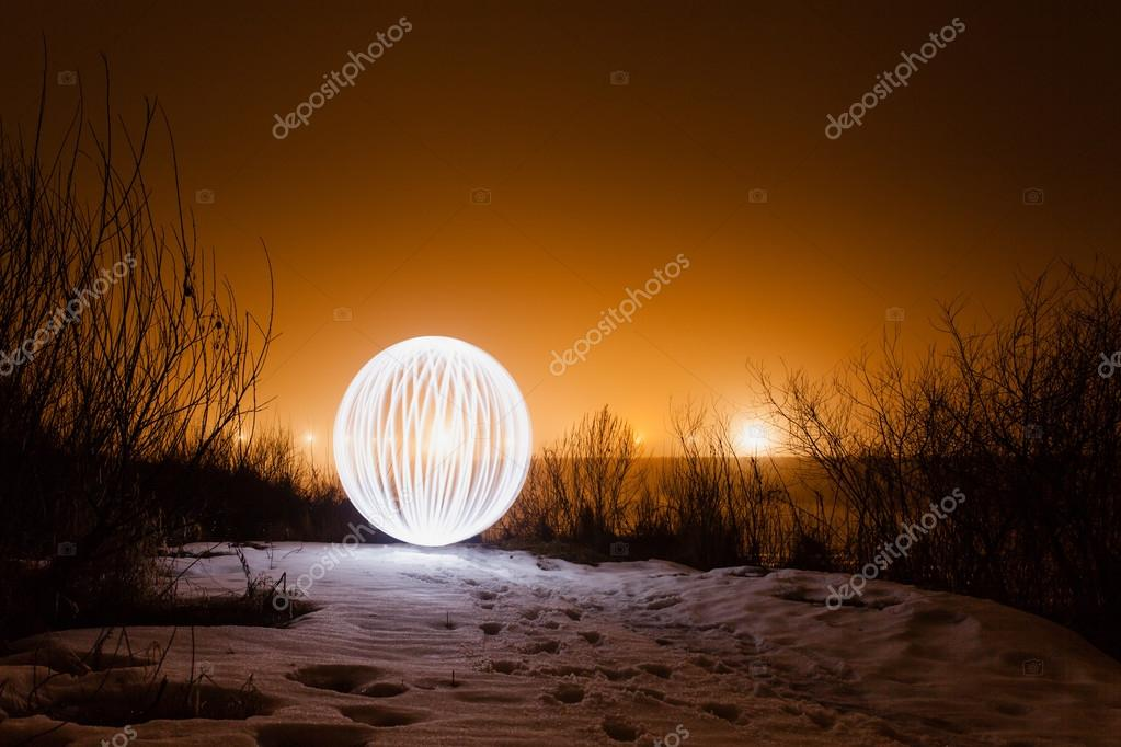 Glowing ball on the banks of the river in the early spring on a background of the night sky glowing