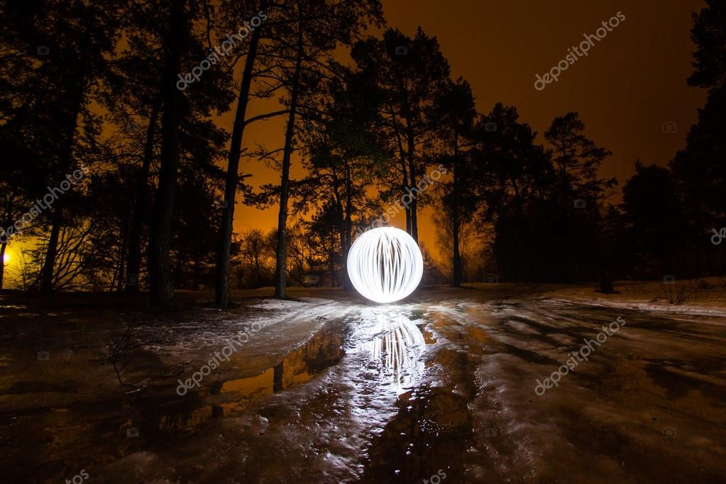 Glowing ball is reflected in the puddles on the melting ice in the spring forest