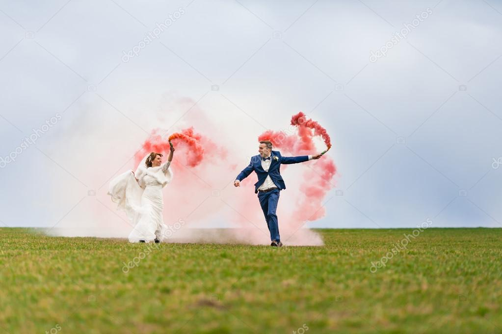 The bride and groom running through the field with red smoke bombs