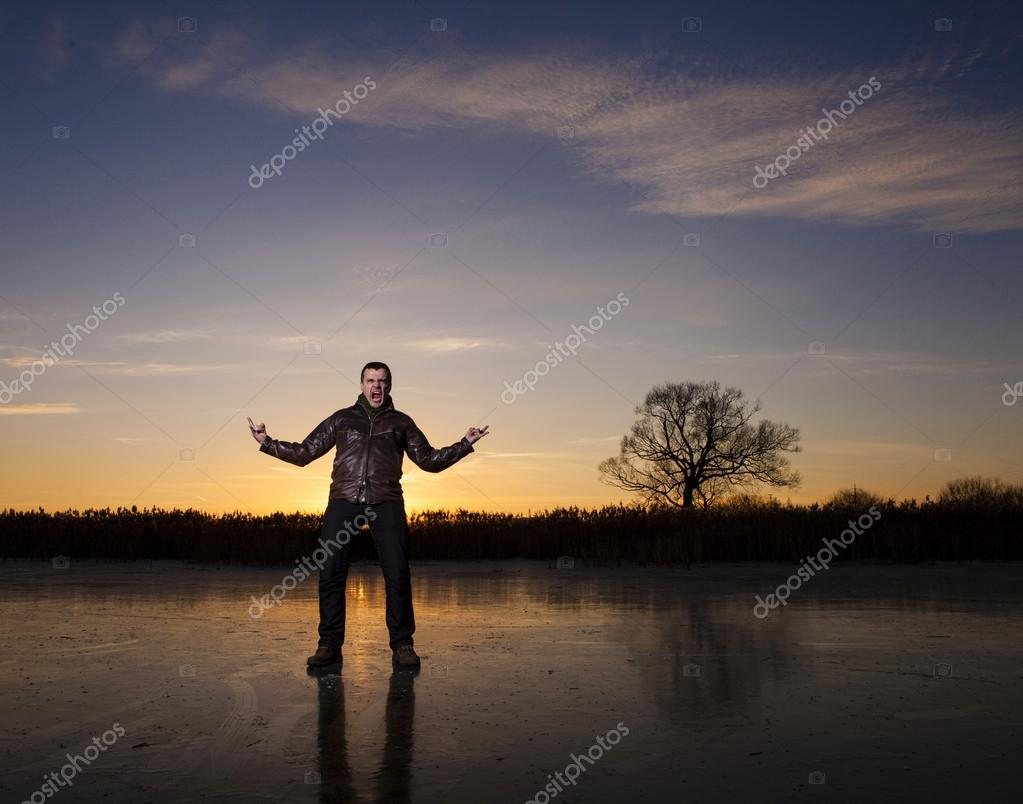 man standing on a frozen lake