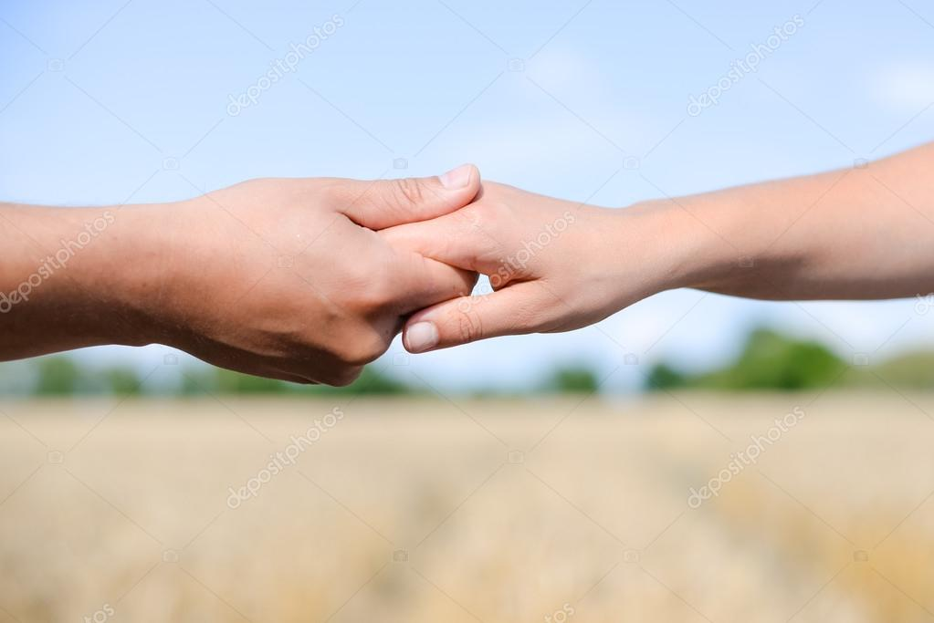 Handshake on outdoors blurred abstract nature background, image closeup