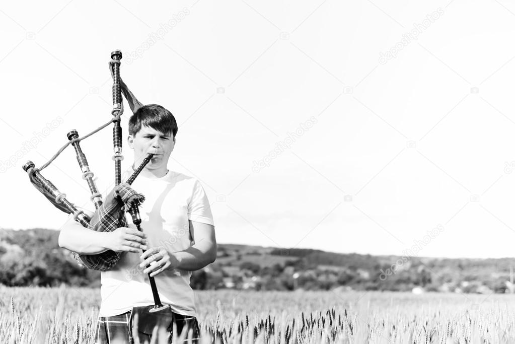 Black white photography of man enjoying playing pipes in Scottish traditional kilt on green outdoors copy space summer field
