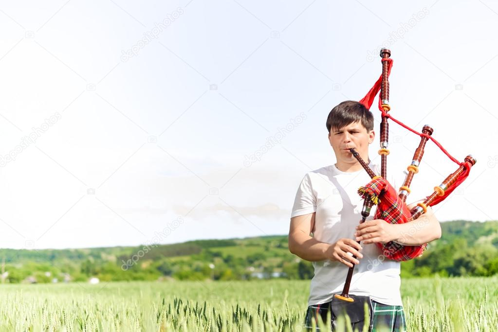 Picture of young man playing pipes in national uniform on green summer outdoors copy space background